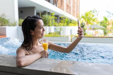 Woman taking selfie in swimming pool