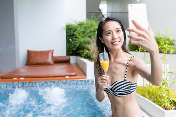 Woman taking selfie in jacuzzi