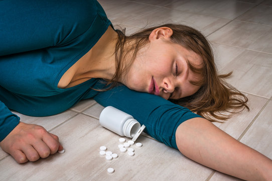 Woman lying on the floor after an overdose of pills