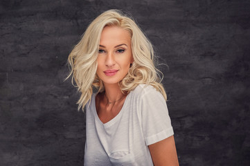 Portrait of blond female over grey background.