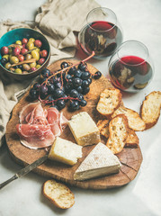 Wine and snack set. Variety of cheese, olives, prosciutto, roasted baguette slices, grapes on wooden board and glasses of red wine over grey marble background, selective focus, vertical composition