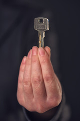 Real estate broker or agent offering house key