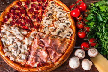 Yummy baked pizza with mushrooms, ham, chicken and sausages on wooden background with ingredients, top view. Restaurant menu photo.