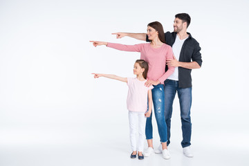 Happy young family standing together and pointing away with fingers on white