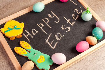 "Easter composition of colored eggs, the Easter Bunny and the inscription ""Happy Easter"""