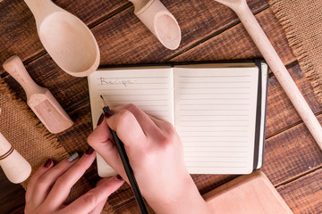 Woman hand write a recipe in cookbook. Book for recipe around utensils on wooden background.