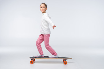 side view of smiling girl riding skateboard on white