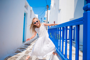 Cute girl in blue dress at street of typical greek traditional village on Mykonos Island, in Greece