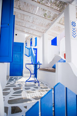 Beautiful terrace with blue chair and table, stairs and flowers. Beautiful terrace exterior with...