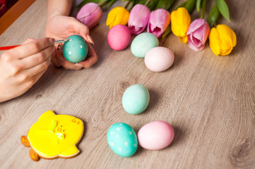 Hands on background wooden tablegirl paints the Easter eggs, preparing for the holiday, decor