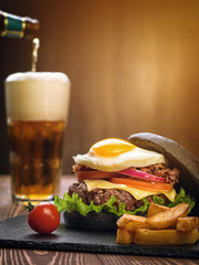 Black burger with an egg on a stone plate.