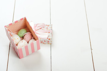 Pastel colored easter eggs in a gift box over white wooden background.