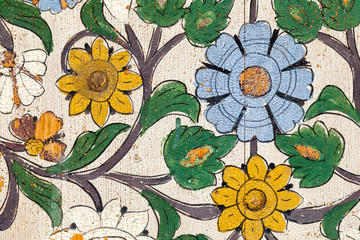 Detail of very old painted flowers and leaves on wood. Morocco. Close up cracked and peeling texture