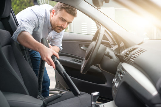 Man vacuum cleaning his car