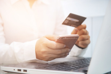 Business man use smart-phone and holding credit card for pay money by online shopping website with laptop computer. technology. online payment. social.