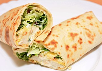 Tortilla wraps with chicken nuggets, fresh vegetable and salad.