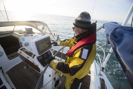 Man Operating Navigational Screen On Sail Boat In Sea