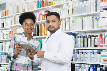 Confident Chemist Holding Digital Tablet By Customer