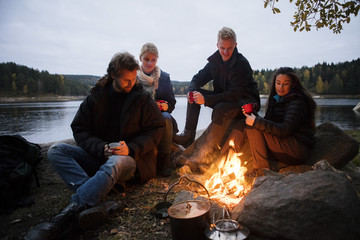 Friends With Coffee Cups Sitting Near Campfire