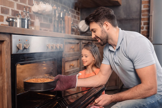 'Side view of smiling father and daughter taking cake from oven