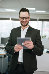 Vertical image of Bearded business man using tablet computer
