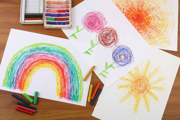 Drawing with pastel crayon. Crayon pieces and drawings (rainbow, sun, flowers) on table.