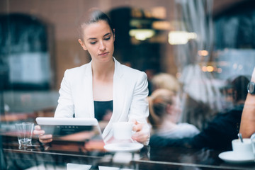 Millennial young businesswoman using tablet computer coffee shop