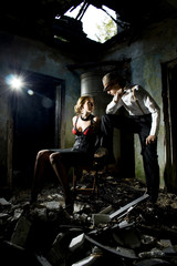 Conceptual photo of murderer and victim. Young woman is sitting on a chair with bound hands and man is standing next to her with gun in hands. They are dressed in retro style. Ruined place.