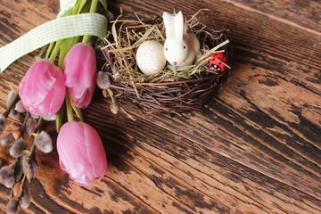 Rosa Tulpen mit Weidekätzchen, Osterhase und Ostereier auf rustikalem Holztisch