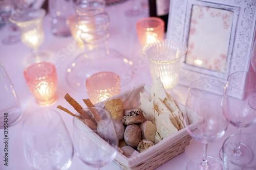Tavolo finemente apparecchiato per cena di gala con candele e in primo piano cesto con diversi - Diversi tipi di pane ...