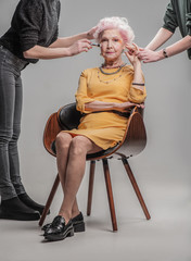 Modern old lady sitting on wooden chair in studio