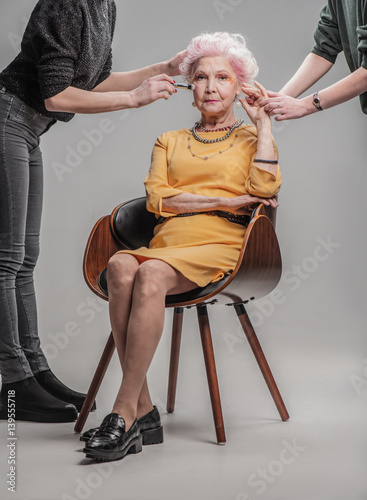 Modern old lady sitting on wooden chair in studio  sc 1 st  Fotolia.com & Modern old lady sitting on wooden chair in studio