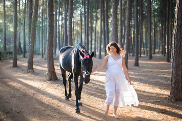 Portrait of Pregnant young woman enjoying in the forest