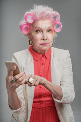 Trendy stylish old lady holding cellphone