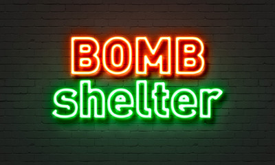 Bomb shelter neon sign on brick wall background.