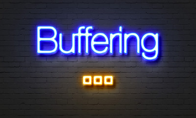 Buffering neon sign on brick wall background.