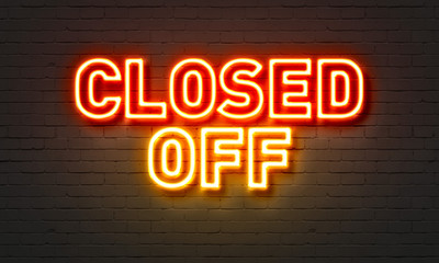 Closed off neon sign on brick wall background.