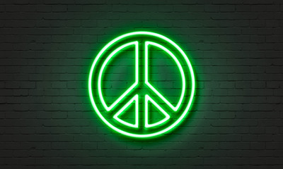 Peace symbol neon sign on brick wall background.