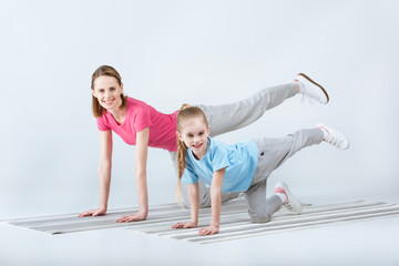 smiling sporty mother and daughter exercising on mats together on white