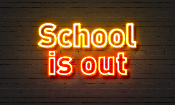 School is out neon sign on brick wall background.