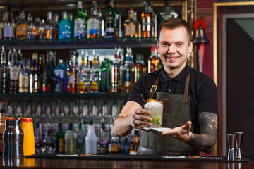 Cheerful bartender gives the cocktail to customer.