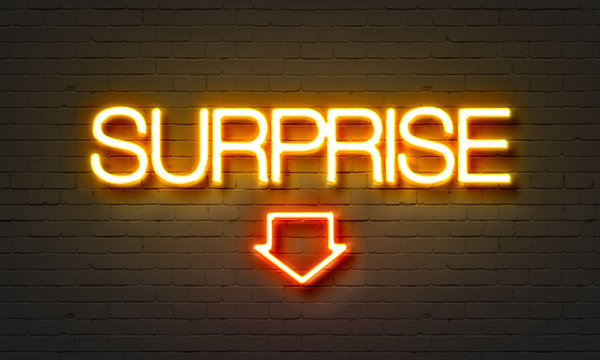 Surprise neon sign on brick wall background.