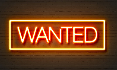 Wanted neon sign on brick wall background.