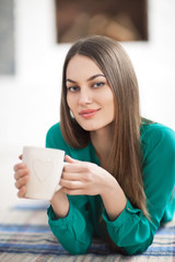 Young beautiful woman lying on plaid with cup of hot coffee in home