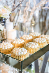 Cupcakes with white cream on the table decorated with white flowers and candles