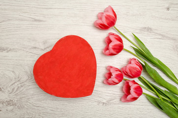 Red box heart shaped and pink tulips on a light wooden background. top view, space for text