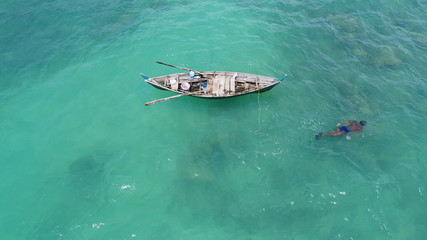 Aerial top view of boat on the sea and fisherman in the water hunting