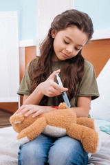 portrait of girl making injection to teddy bear in hospital chamber