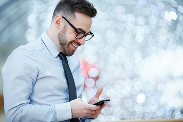 Side view portrait of modern businessman wearing glasses, shirt and tie smiling joyfully while reading text message from smartphone against blurred office background