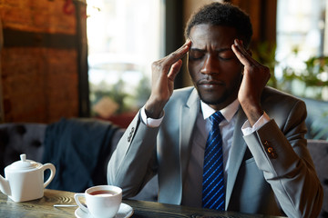 Portrait of handsome African American man suffering from headache and exhaustion at table in modern restaurant during coffee break